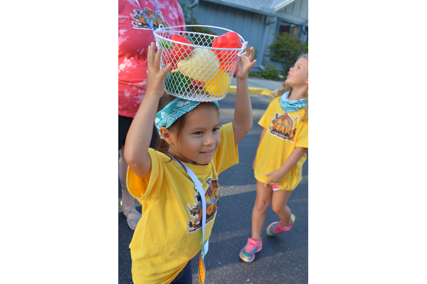 Makynzie Birch, 5, tries to balance a bucket on her head. She jumped up and down when her friends were successful doing it.