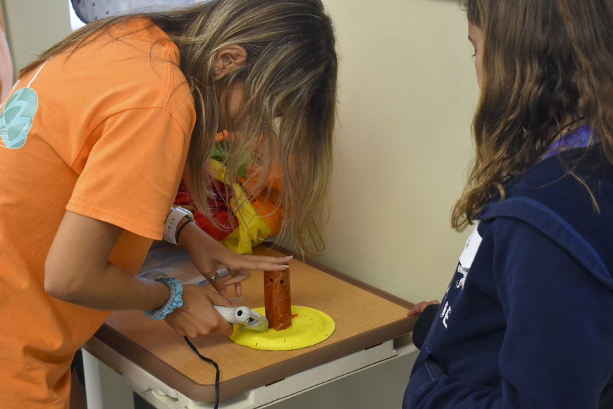 Morgan Meyer, a Mote education specialist, helps Laila Pumarejo with her coral polyp.