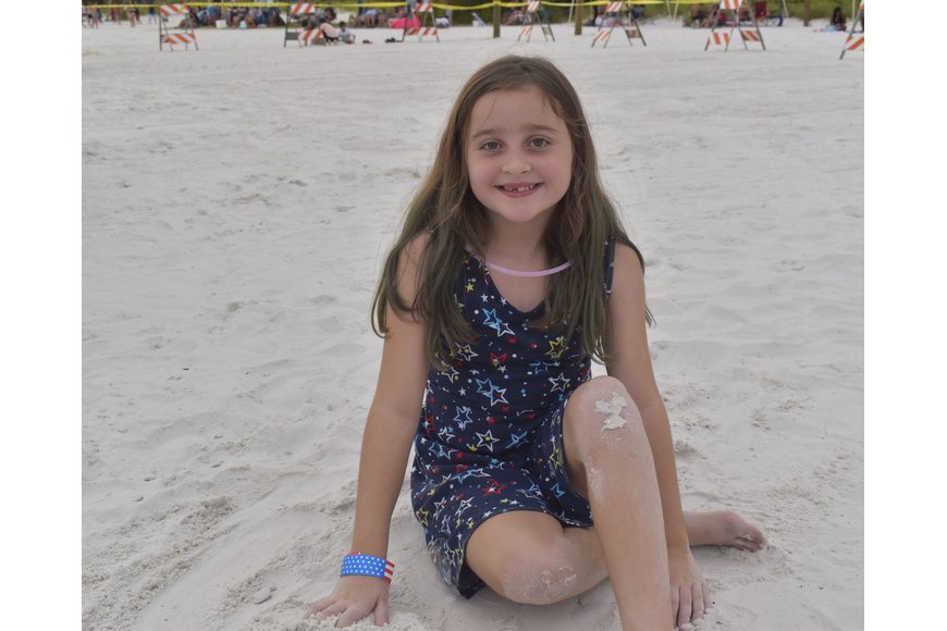 Madison Miliam, 7, lounges in the sand before the fireworks begin.