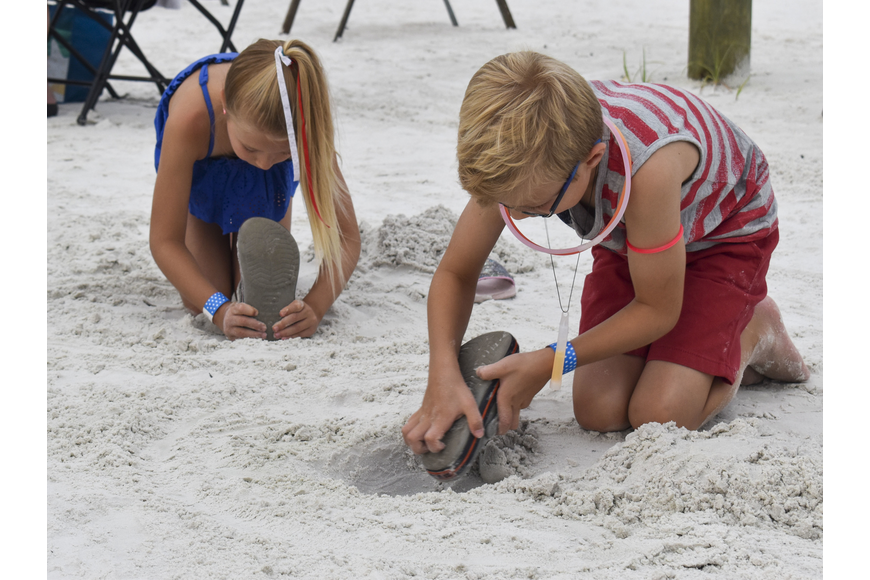 Ashely and Josh Eisenacher play in the sand before the fireworks begin.