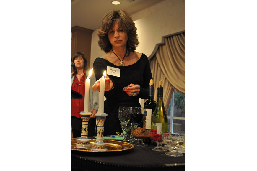 Nancy Swart lights the candles.
