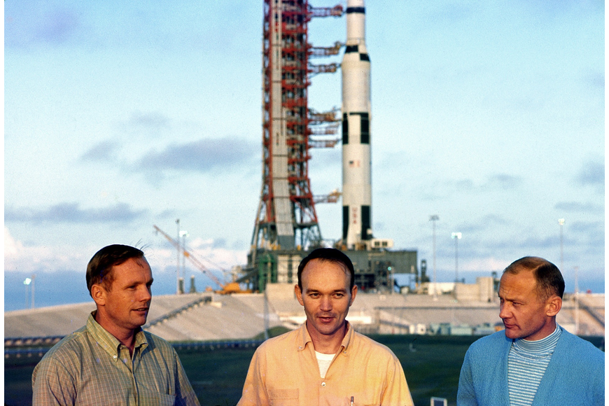 Neil Armstrong, Mike Collins and Buzz Aldrin talking with reporters in front of their Saturn V after it was rolled to the launch pad on May 20, 1969.
