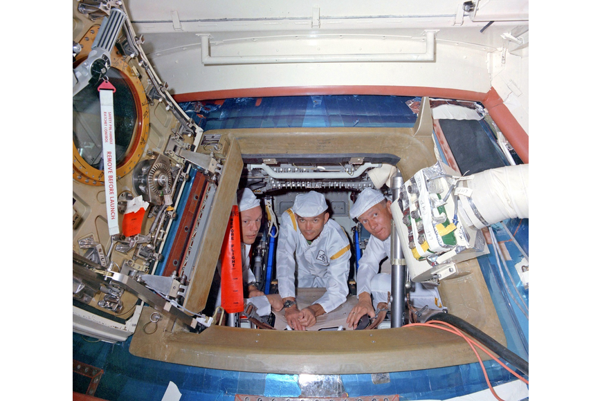 The Apollo 11 crew aboard their command module atop the Saturn V on June 10, 1969. Armstrong, Collins and Aldrin are wearing protective coveralls as they perform a