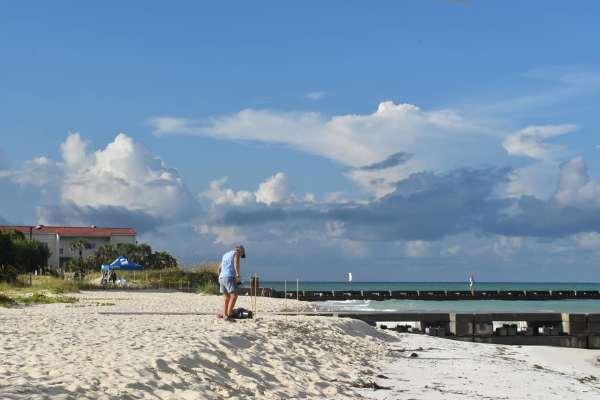 Mike Herron, a member of the Longboat Key Turtle Watch, checks out a nest with the Surfrider tent in the background.
