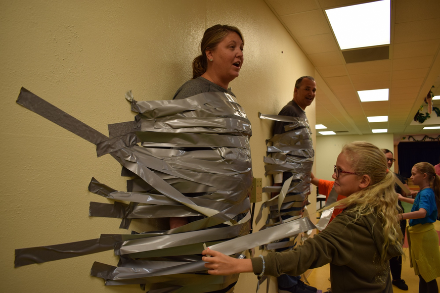 Braden River Elementary School fourth-grader Caitlin Motherway, 9, right, is one of the about 252 students who were able to tape Assistant Principal Krista Francies to a wall as a reward for completing their summer learning.