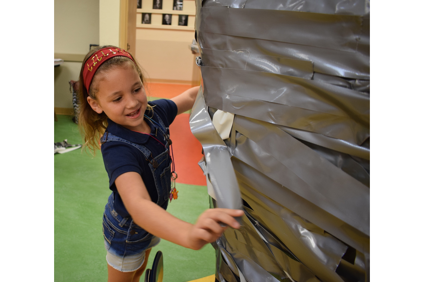 Braden River Elementary School third-grader Lillian Chandler, 8, places a piece of tape onto Assistant Principal Krista Francies.