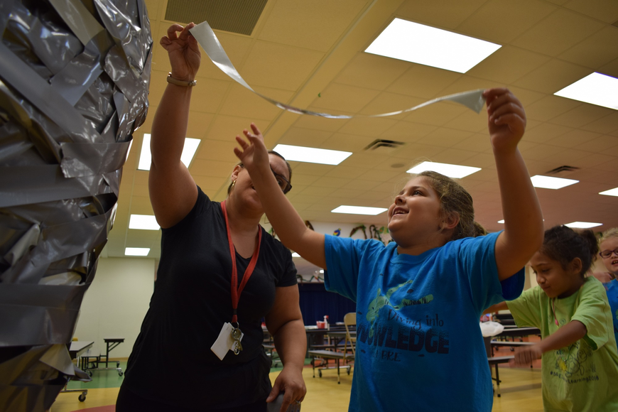 Braden River Elementary School paraprofessional Salvatrice Rizzo, left, helps second-grader Rosemary Aronin, 7, attach a piece of tape to Principal Joshua Bennett's shoulders.