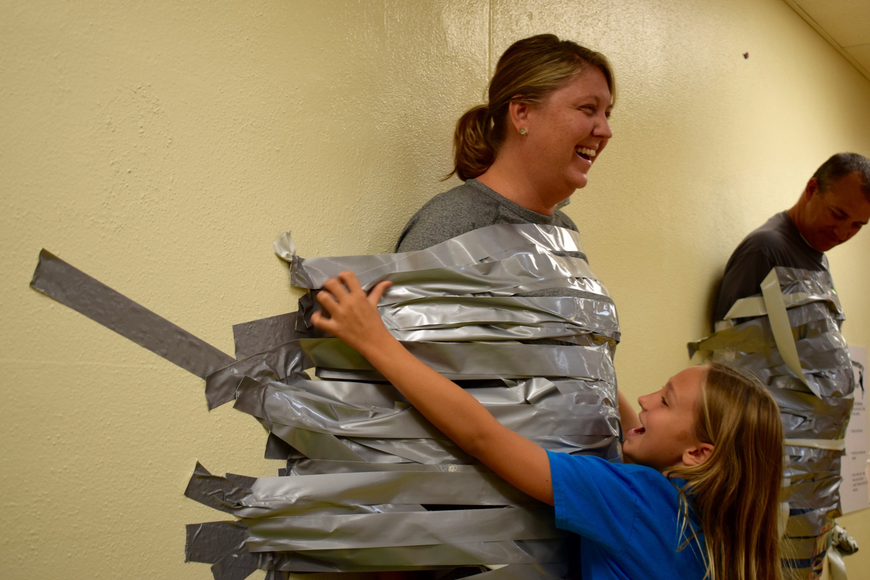 Braden River Elementary School fourth-grader Kylee Francies, 9, right, tapes her mom, Assistant Principal Krista Francies, to a wall. Kylee Francies said it was