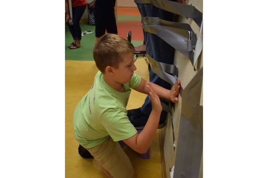 Braden River Elementary School fifth-grader Logan Santiago, 10, pounds tape to the wall to make sure it's secure.