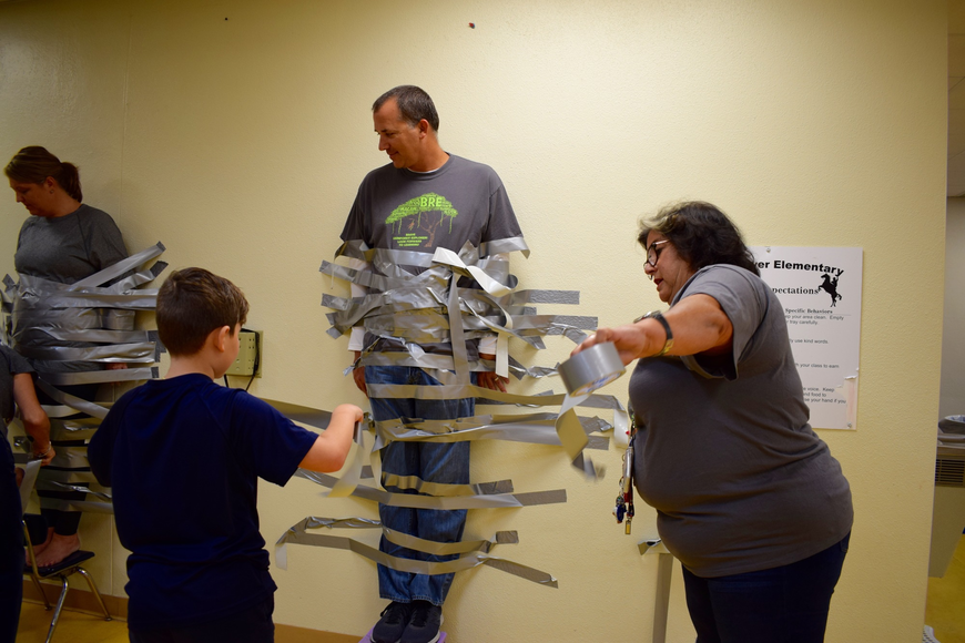 Braden River Elementary School fifth-grader Jonathan Lopez, 10, left, goes to tape Principal Joshua Bennett, center, to the wall while ESOL paraprofessional Barbara Grimes, right, rips off more tape to hand to students.