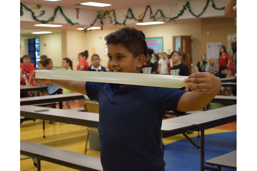 Braden River Elementary School fourth-grader Roshan Leonardo, 9, stretches out his piece of tape before placing it on Assistant Principal Krista Francies.