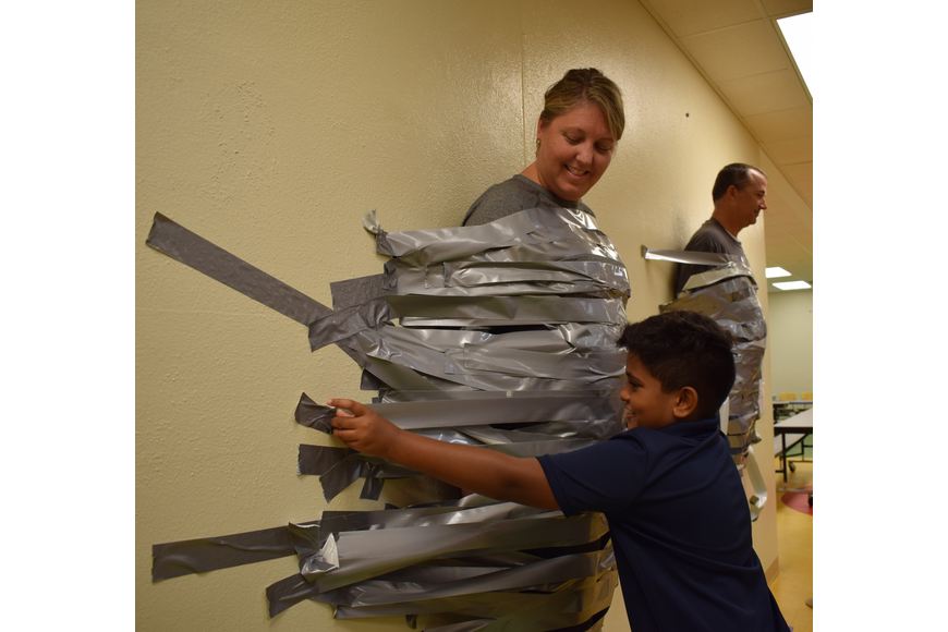 Braden River Elementary School fourth-grader Roshan Leonardo, 9, right, places a strip of tape across Assistant Principal Krista Francies.
