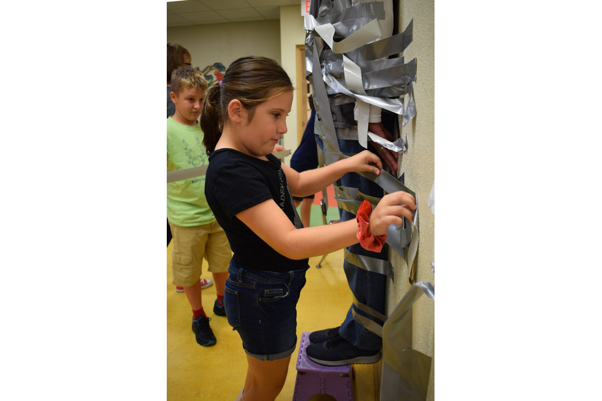 Braden River Elementary School fifth-grader Emma Donnelly, 10, focuses on securing a piece of tape to the wall to ensure Principal Joshua Bennett won't come off the wall.