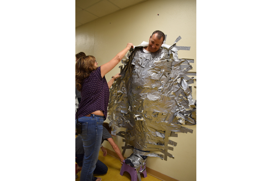 Braden River Elementary School student support specialist Michele Jones starts to peel Principal Joshua Bennett off the wall after about 252 students taped him to it.