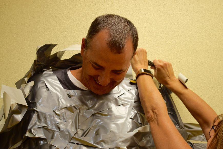 Braden River Elementary School Principal Joshua Bennett smiles as student support specialist Michele Jones works to peel him off the wall and free him from more than 252 pieces of duct tape students placed on him.