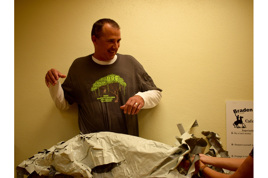 More than 252 pieces of duct tape are peeled off Braden River Elementary School Principal Joshua Bennett. Friday was Bennett's first time being taped to a wall, which was a reward for students who completed their summer learning.