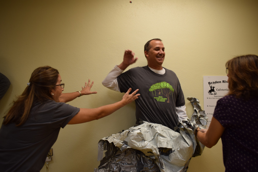 Braden River Elementary School kindergarten teacher Frances Vila, left, reaches out to Principal Joshua Bennett, center, as he starts to fall while student support specialist Michele Jones, right, peels the tape off Bennett.