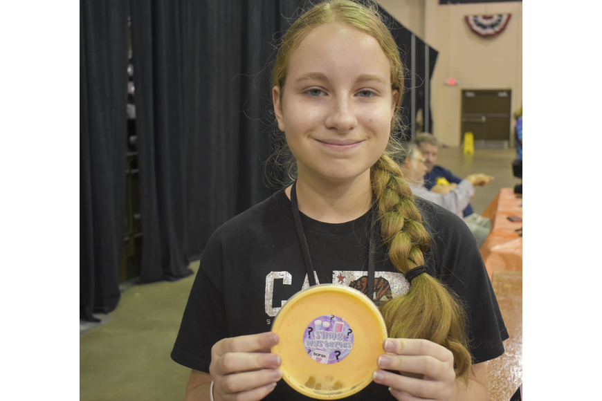 Kristina Burmeister waits in the slime trading center to share her homemade candy corn slime from Slime Mysteries.