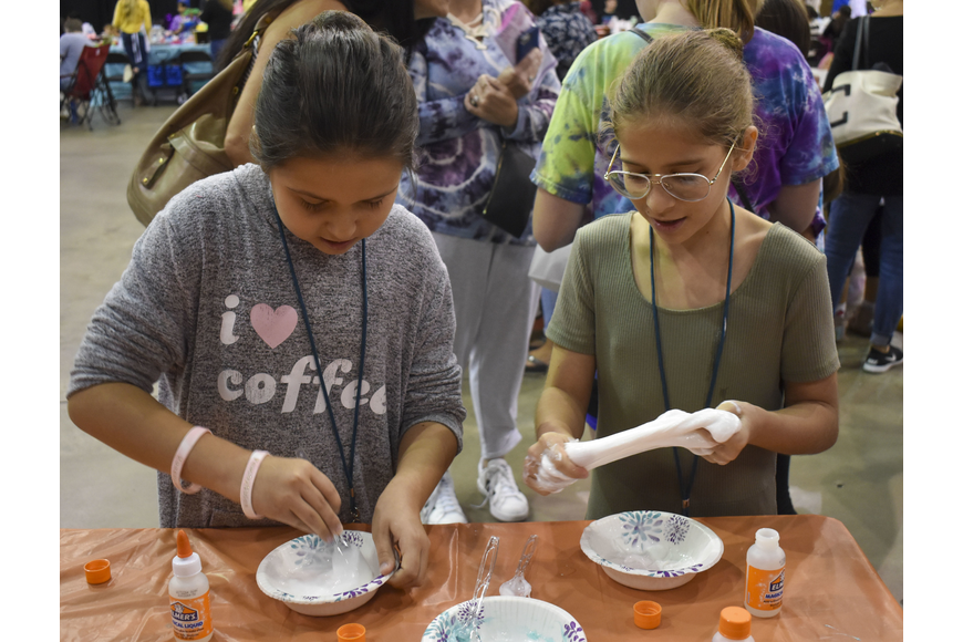 Olivia Schaedlerluera, 10, and Vanessa Oser, 10, mix together their slimes.