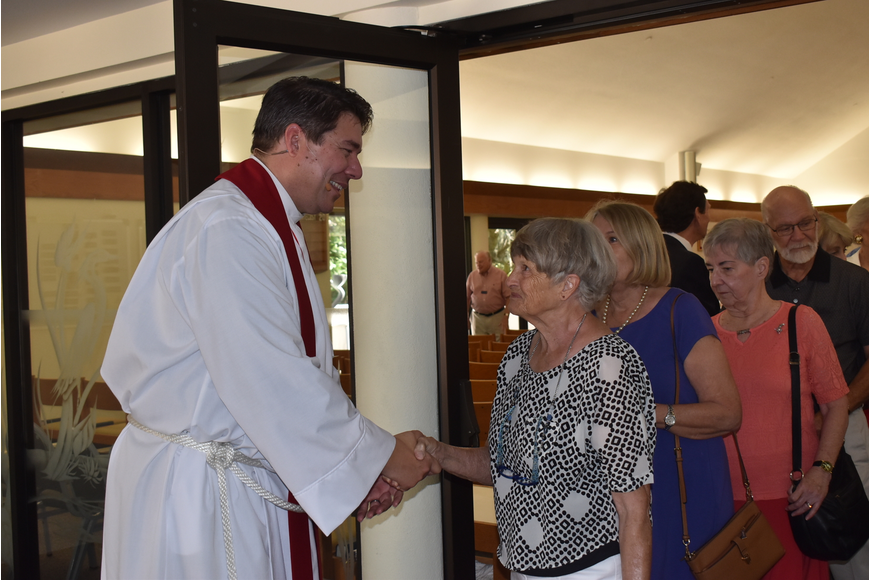 Father Dave Marshall shakes hands with his congregants as they congratulate his new position.