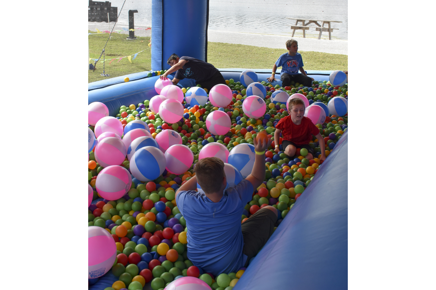 A group of kids hide from the heat in the ball pit.