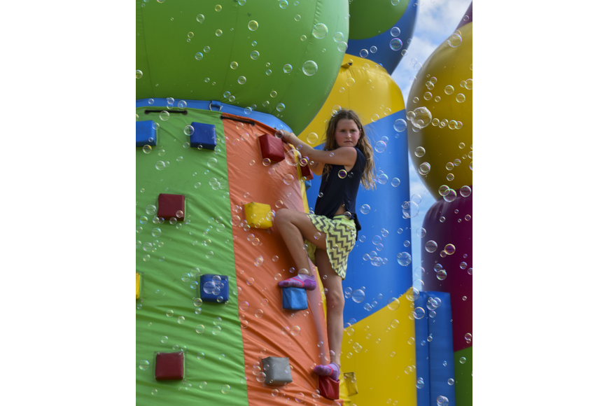 Kenzi Kondrup, 11, looks out from the top of the climbing wall.