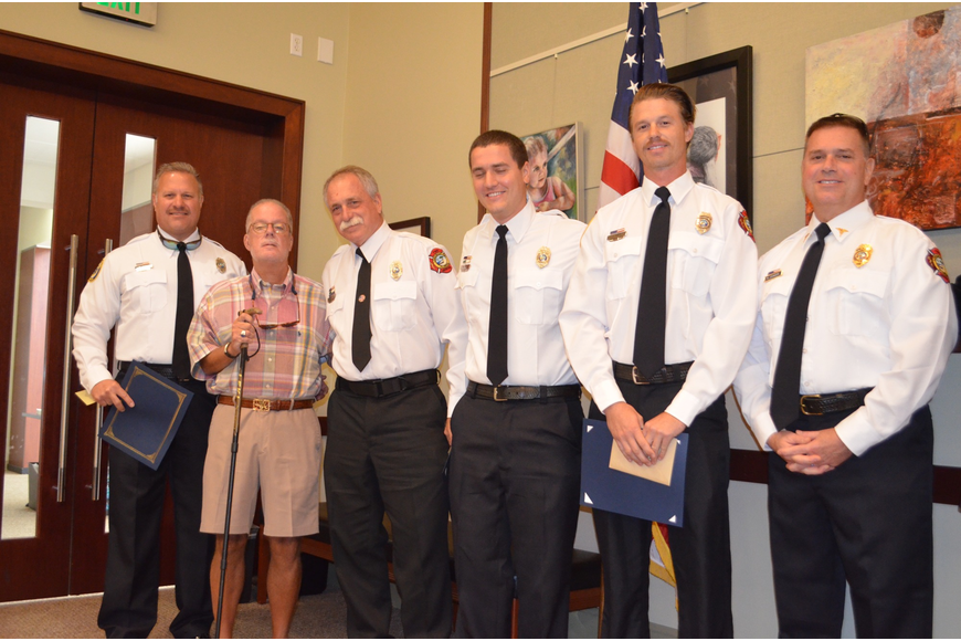 McLean, second from left, pinned Phoenix Awards to the men who saved his life: Ron Koper, Jeff Bullock, William Lewis and Jamison Urch. Standing with them is  department medical director Dr. Mike Johnson.