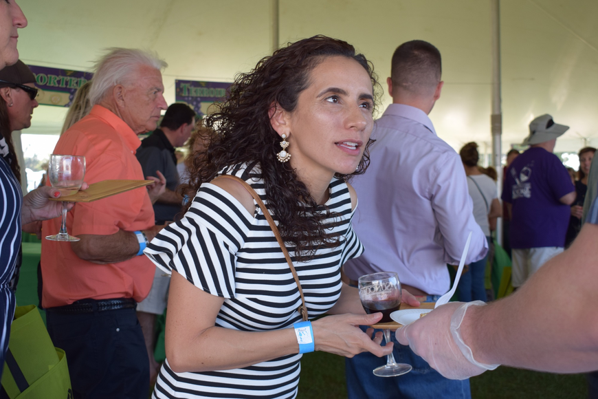 Sarasota resident Mary Garcia gets a sample of food during the Suncoast Food and Wine Fest. Garcia and her husband, Miguel, said the fest is a social event where they run into people they know while also meeting new people.