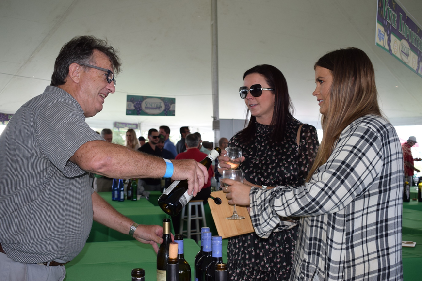 Fran Schoepfer, a sales manager for Vine Importers, gives a sample of Midnight Estate wine to Sarasota residents Lindsey Meshberger and Shannon Lynch.