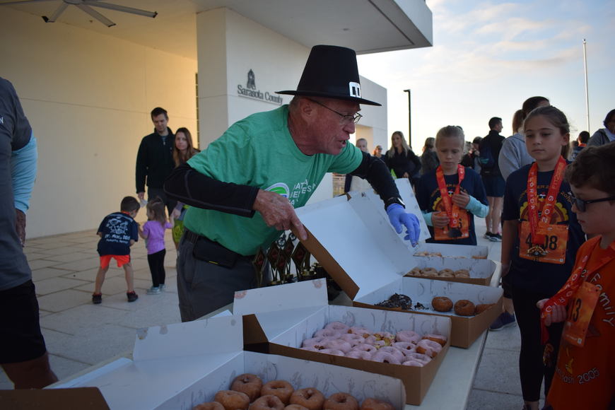 Tara's Lynn Hollabaugh hands out donuts to the children who had finished their race.