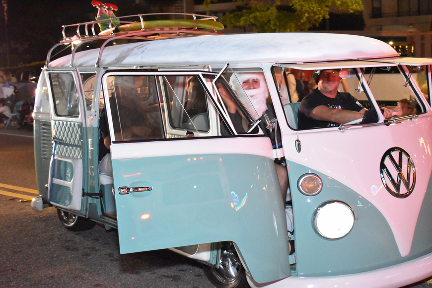 A vintage Volkswagen blasts holiday music through its open doors.