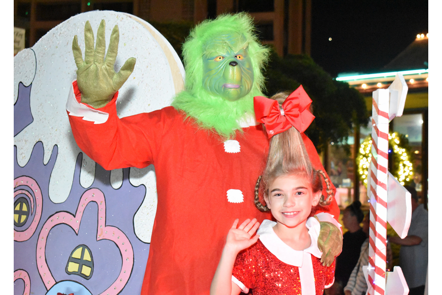 The Grinch and Cindy Lou Who wave to the crowd.