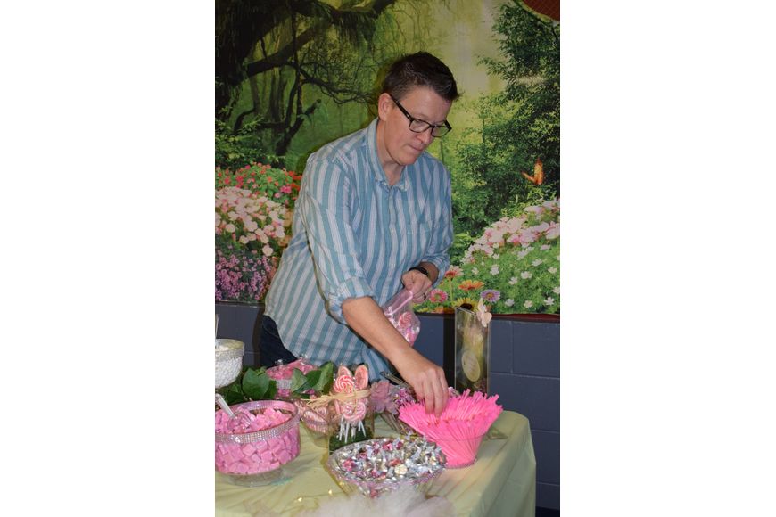 Cary Jones, a co-vice president of the Parent Teacher Organization, prepares a bag of candy from the candy buffet.