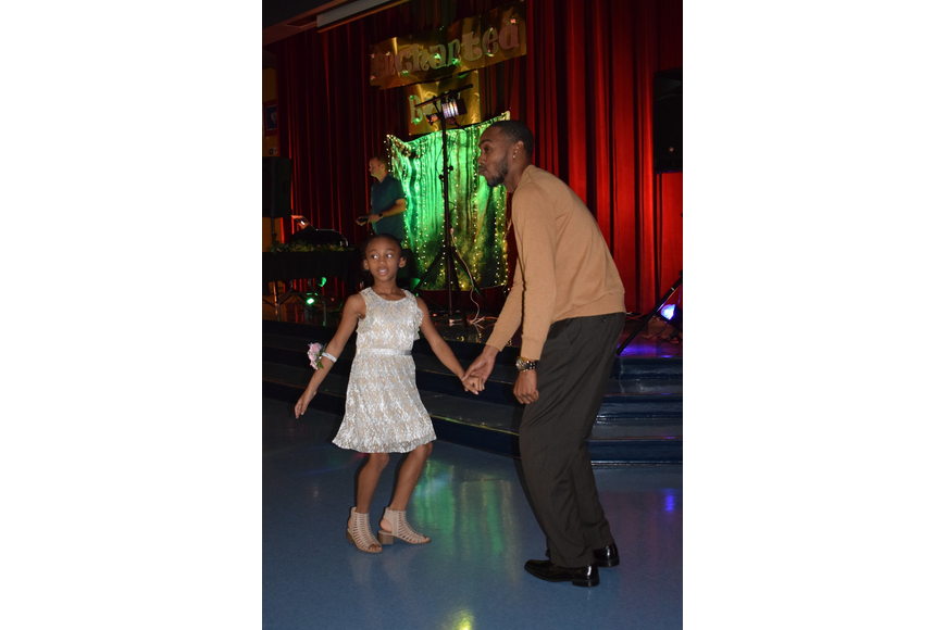 Ali'yana Jones, a third grader, dances with her dad, Donald, at the annual father-daughter dance. Donald Jones says they go to the dance every year and always have a great time.