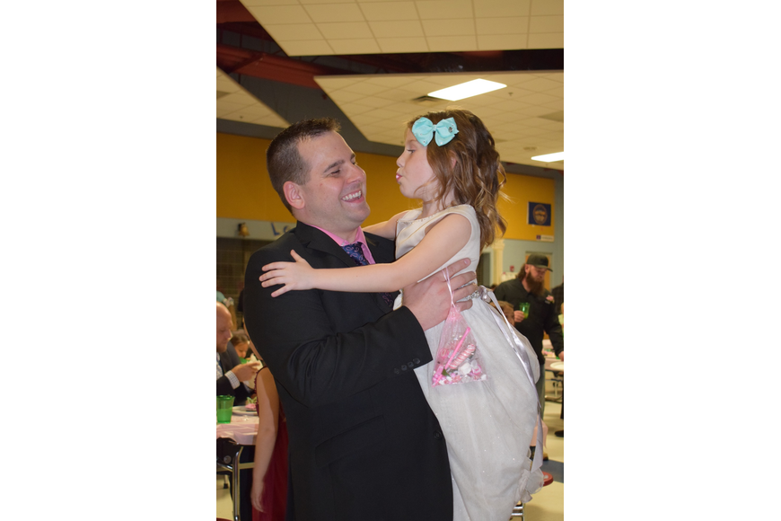 Jason Kinsman holds his daughter Addison, a kindergartner, while dancing to a slow song. This year's dance was the Kinsmans second.