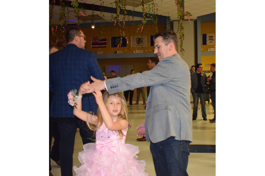 Scarlett Hafner, a first grader, is twirled around by her father, Mark. Scarlett Hafner says the dance is fantastic because you can dance.