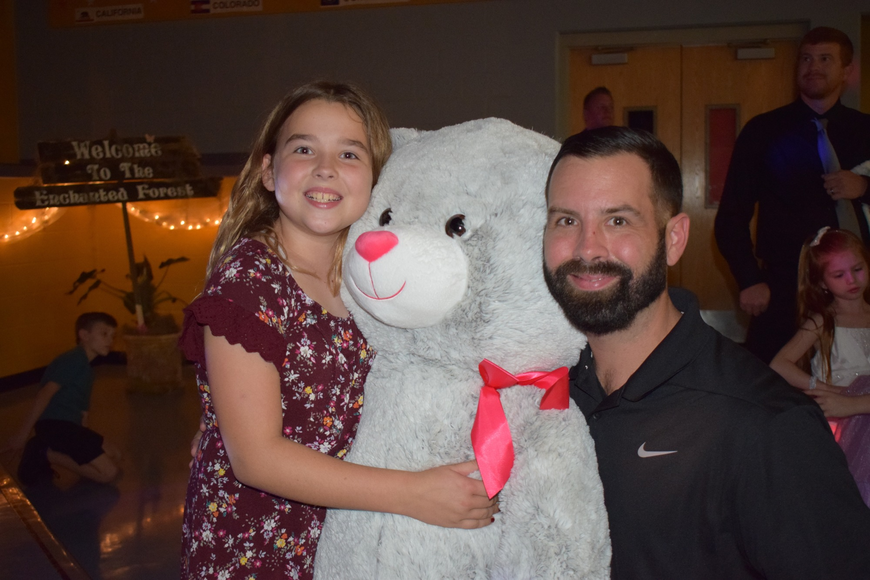 Ava Delvin, a fourth grader, and her dad, Tim, win a giant teddy bear in a raffle.