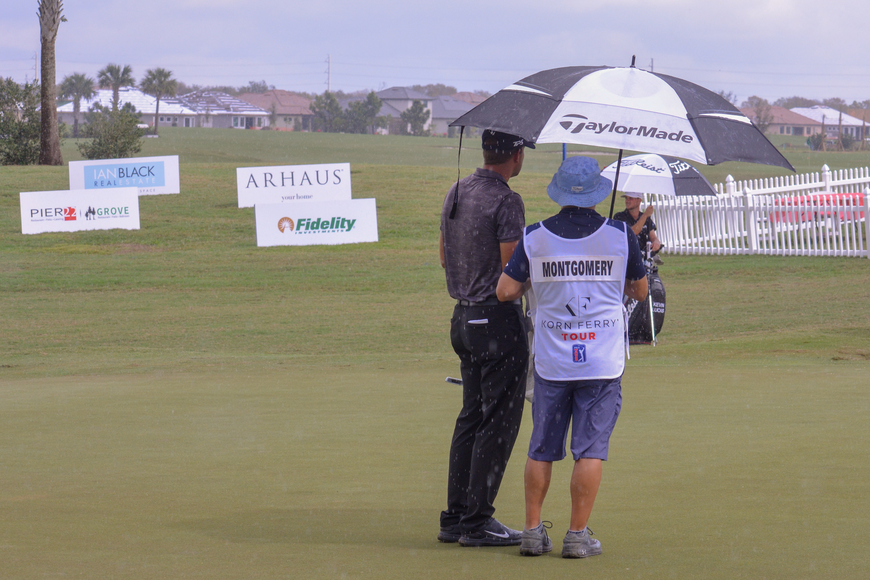 Taylor Montgomery chats with his caddie in the rain at the LECOM Suncoast Classic.