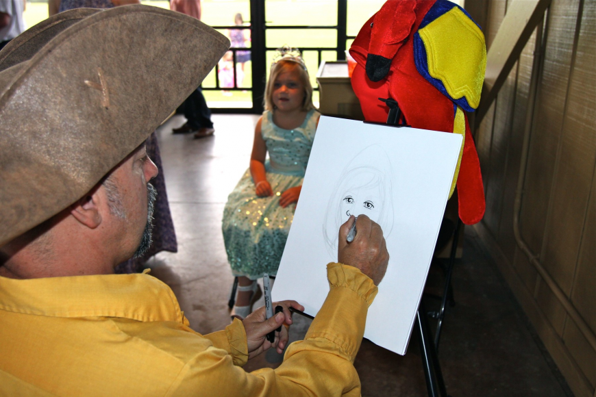 Laine Yahraus, 6, has her portrait drawn by Michael James White.