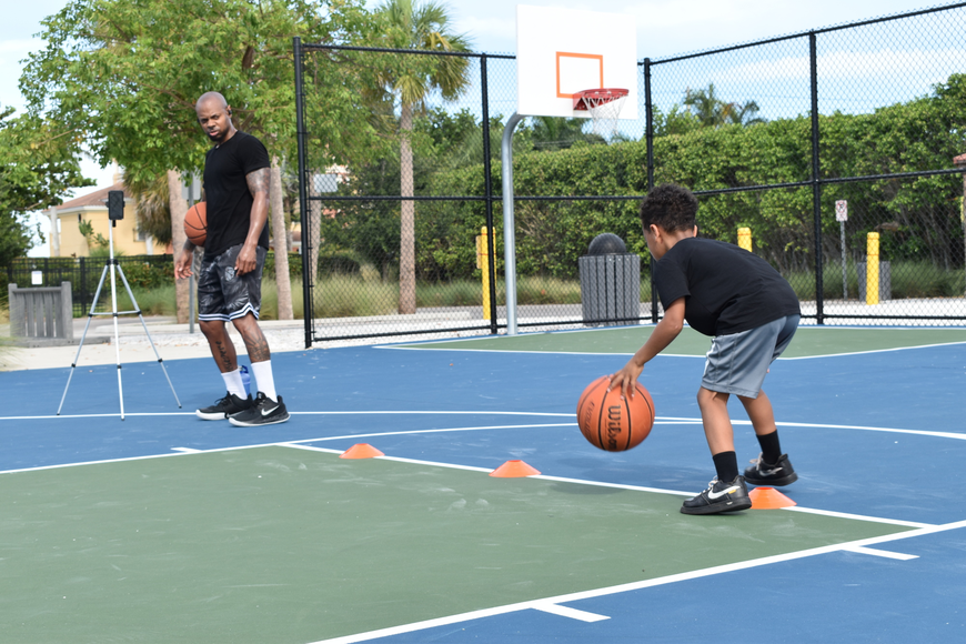 Tim Grant (left) watches his son King Grant (right) perform a dribbling drill.