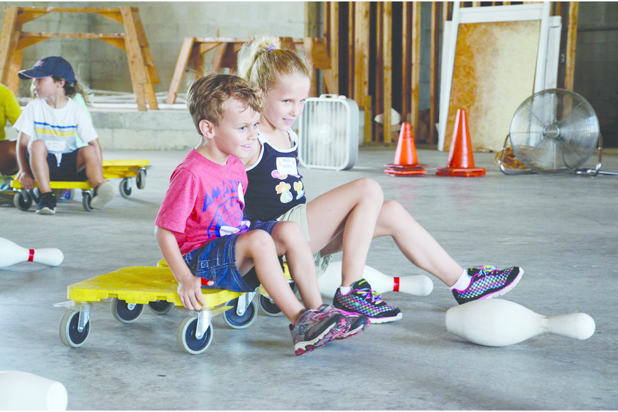 Evan Branson and Madison McCaffery race to knock over a pin at Risen Savior Lutheran Church's Vacation Bible School.