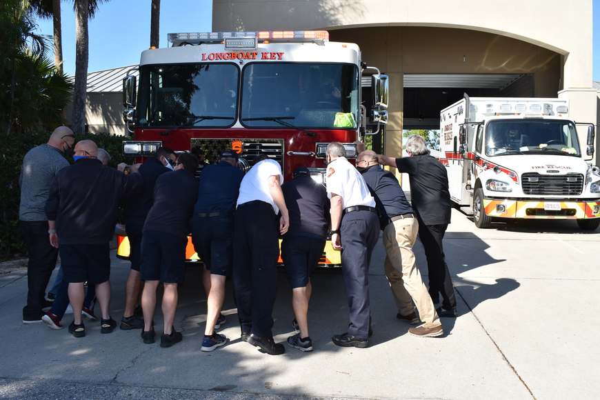 Longboat Key Fire Rescue personnel and town staff push the new fire truck into the bay at 5490 Gulf of Mexico Drive.