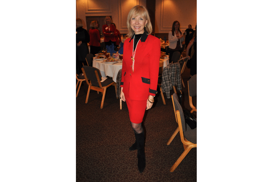 Charlie Ann Syprett wore a red St. John's suit with Stuart Weitzman boots