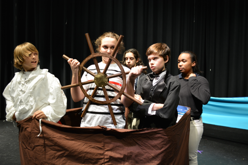 Prince Eric (Phineas Scanlon) argues with Grimsley (Caden Denslow), front right, as Olivia Knego steers the ship.