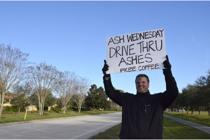 Volunteer Rich Cunningham waves in commuters to get ashes for the holy day.
