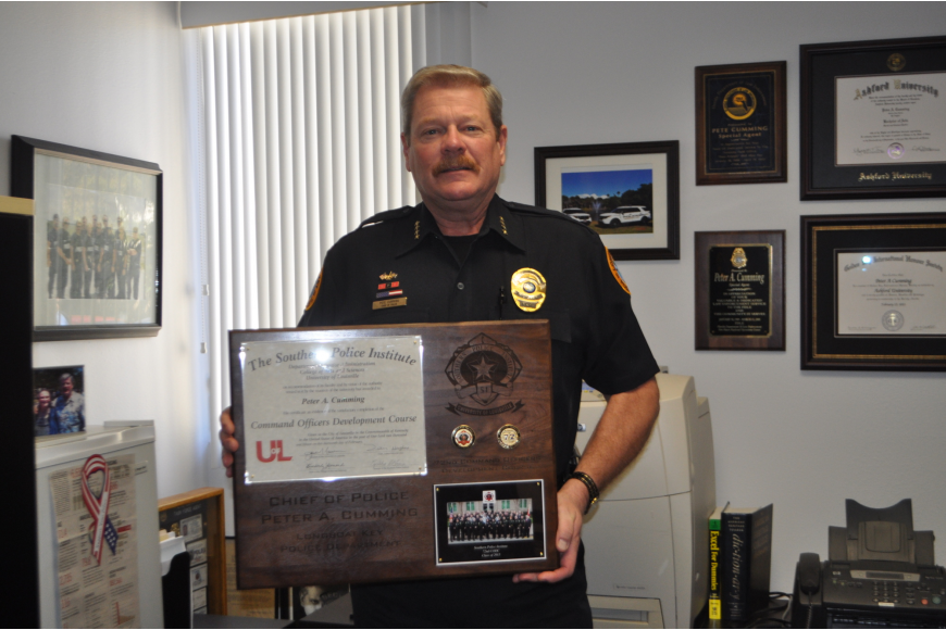 photo of Longboat Key police chief Pete Cumming holding a plaque.
