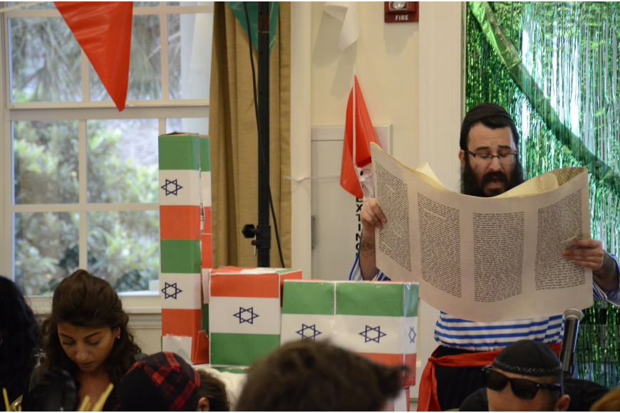 Rabbi Mendy Bukiet reads from the Megillah, or Scroll of Ester, which recounts the salvation of the Jewish people from a Persian vizier.