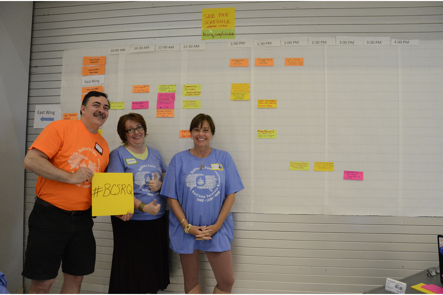 Volunteers Norm Dempsey, Candace Lourdes and Diane Rivers help with the speaker schedule board — anyone attending could sign up to speak about a topic of their choice.