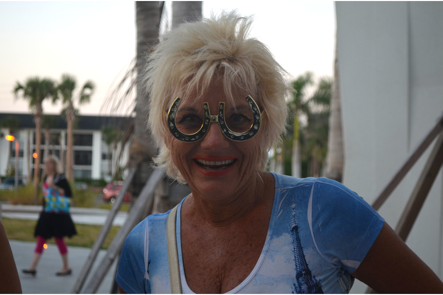 Darina Buettner models a pair of horse shoe glasses outside the photo booth at Sandfest.