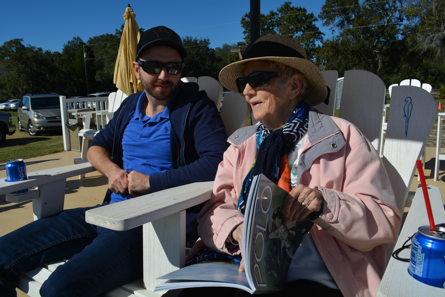 Michael Kirton chats with his grandmother, Marion Walker, who reads the rules of polo during her first match.